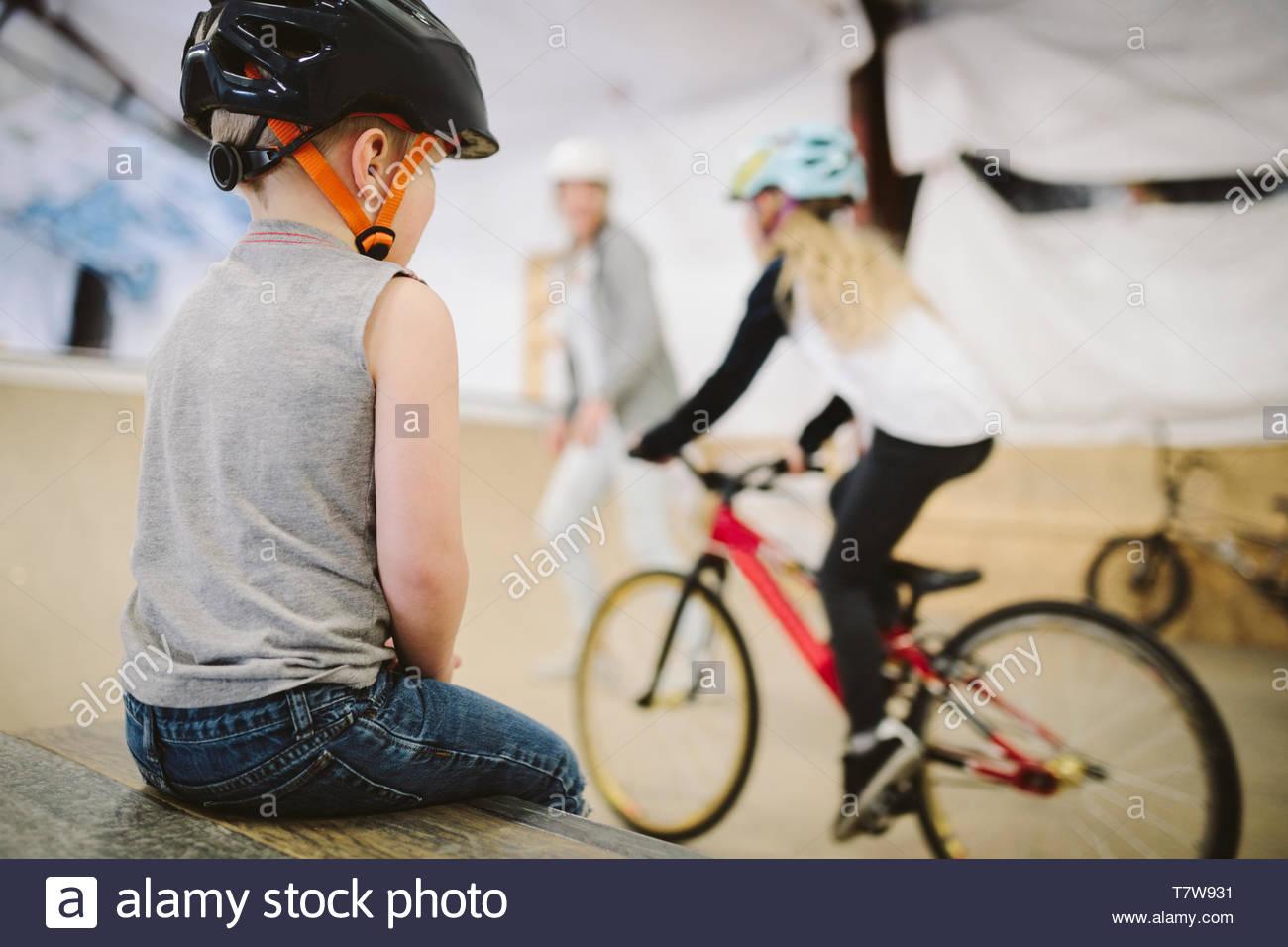 Toddler boy watching sister bike riding at indoor skate park Stock Photo