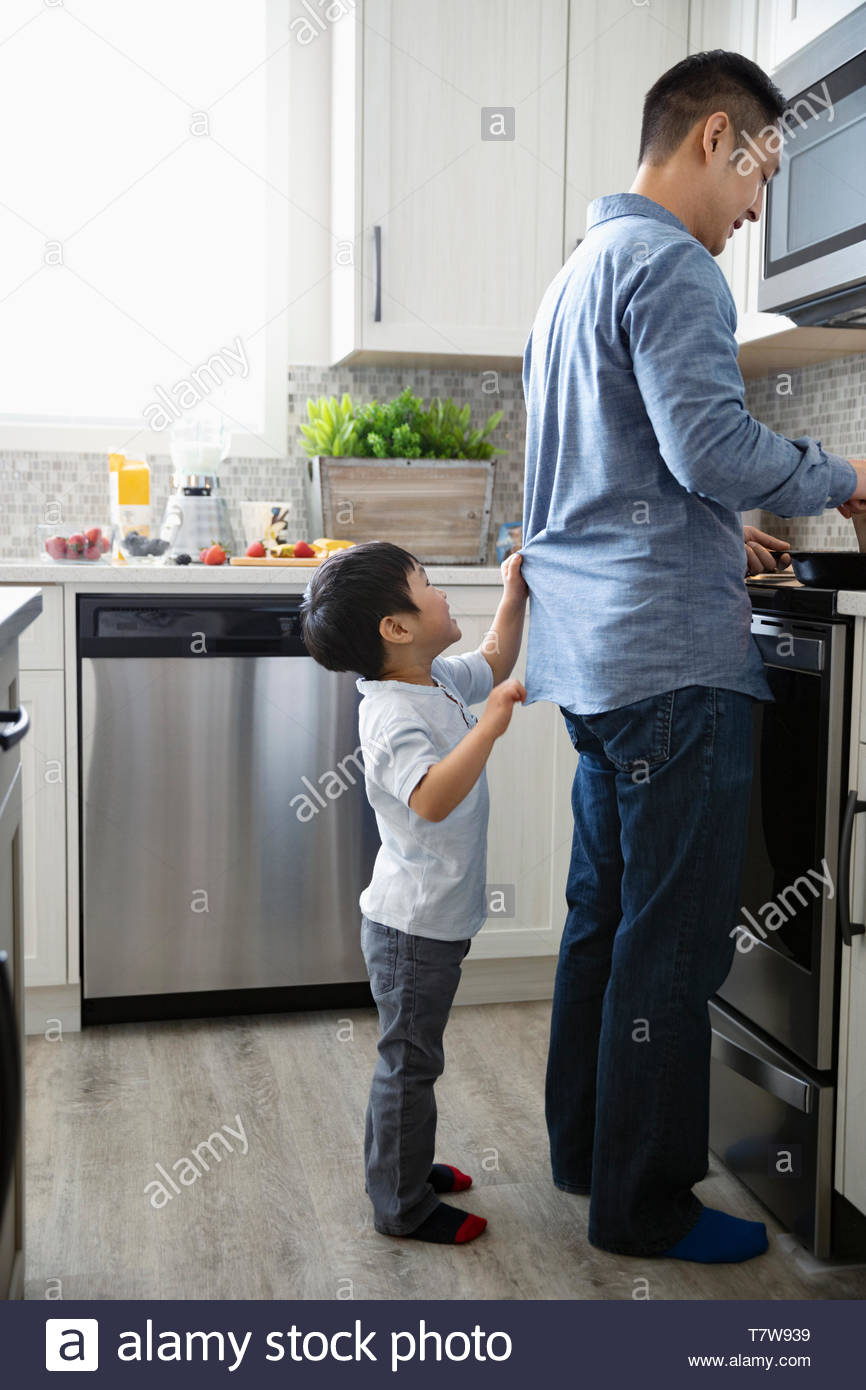 Cute son tugging at father cooking at kitchen stove - Stock Image