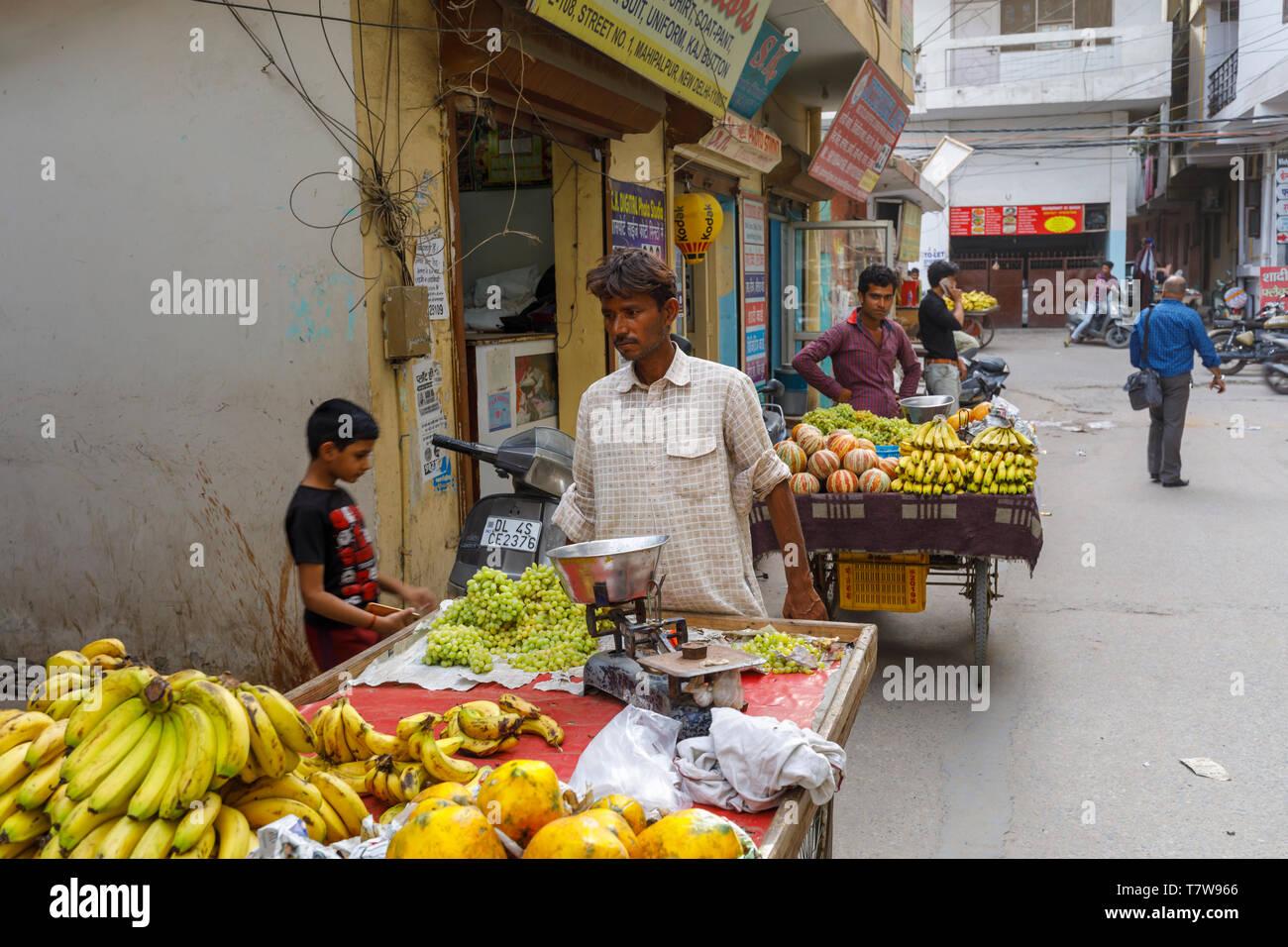 Street scene in Mahipalpur district, a suburb by Delhi Airport in New Delhi, capital city of India: local male street trader at a barrow of fruits Stock Photo