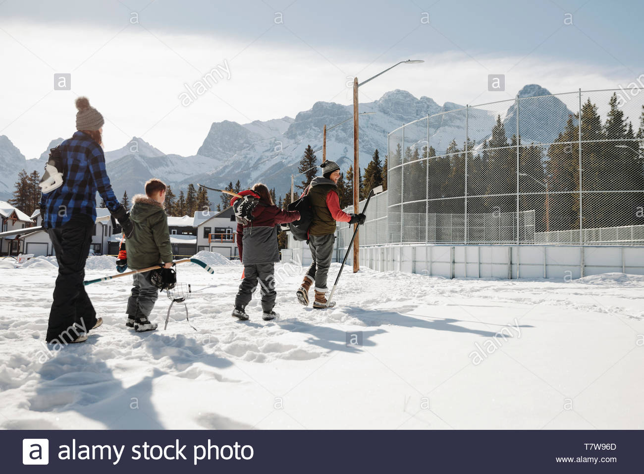 Family walking toward outdoor ice hockey rink - Stock Image
