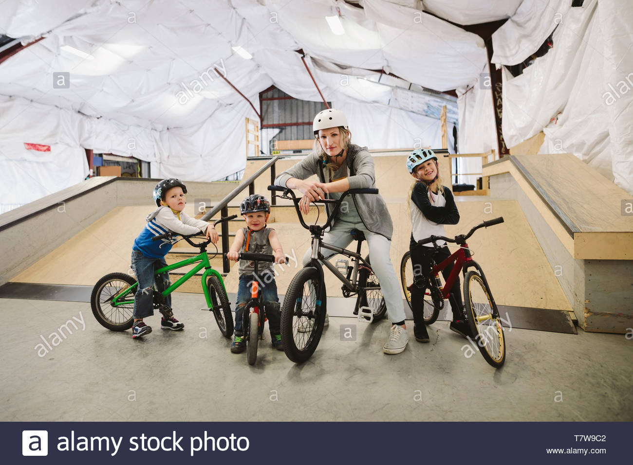 Portrait confident mother and children on bmx bikes at indoor skate park - Stock Image