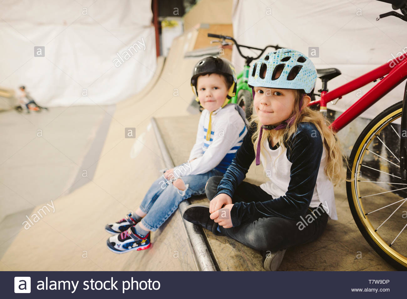 Portrait brother and sister with bmx bikes sitting at top of ramp at indoor skate park - Stock Image