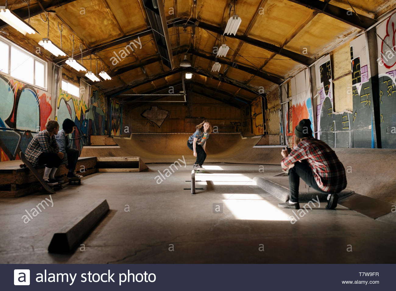 Young woman with camera phone filming friend skateboarding at indoor skate park - Stock Image