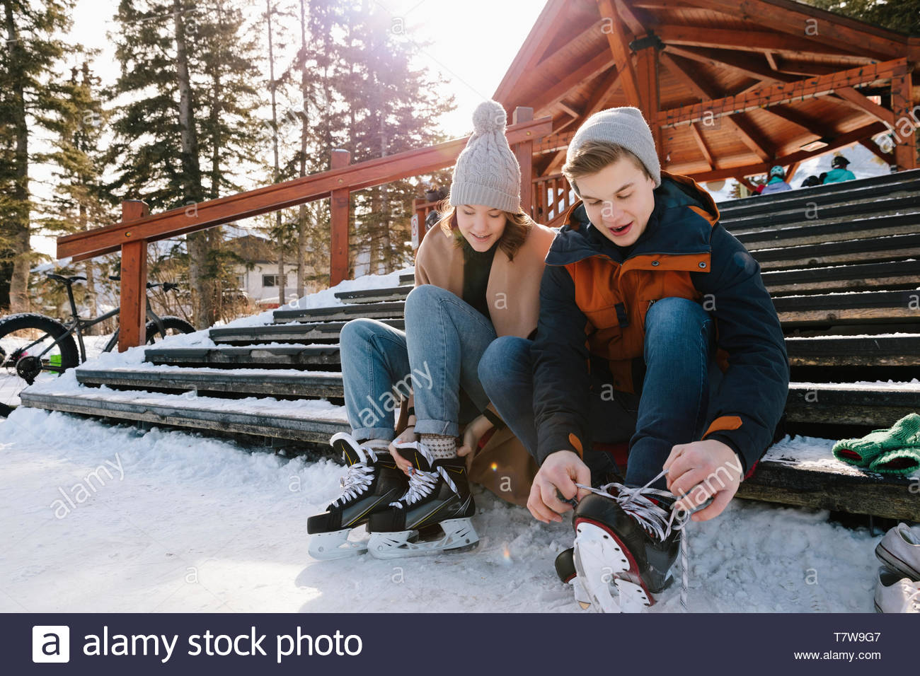 Young couple tying ice skates on snowy steps - Stock Image