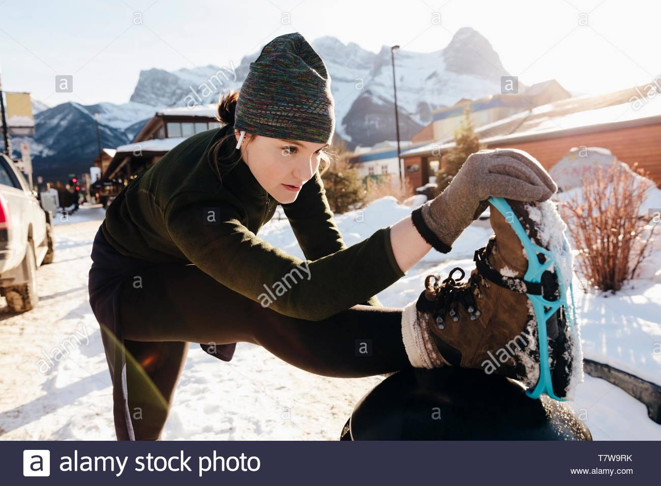 Focused teenage girl runner stretching leg on snowy sidewalk - Stock Image