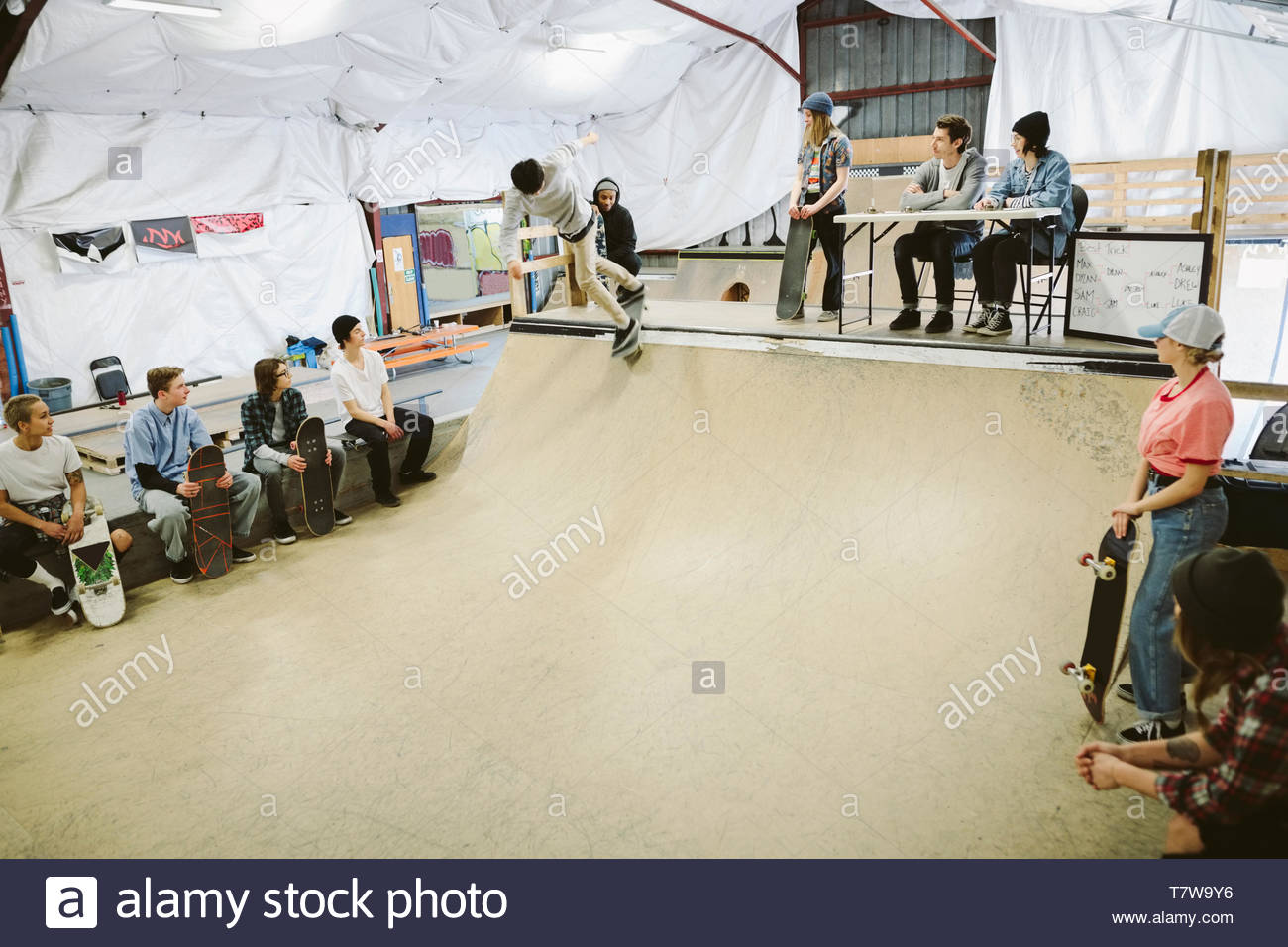 Judges watching skateboard competition from top of ramp at indoor skate park - Stock Image