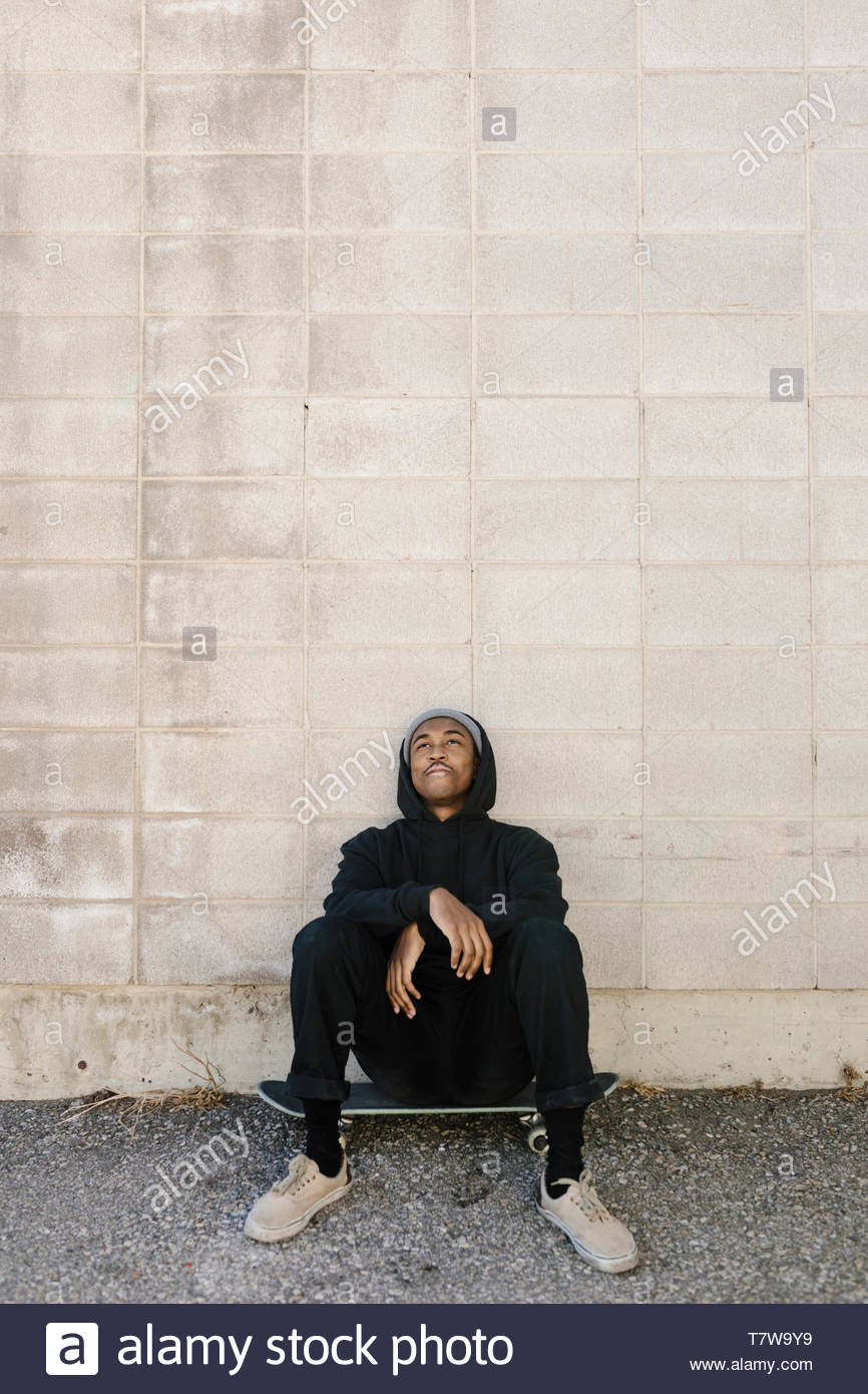 Serene young male skateboarder sitting on skateboard against concrete wall - Stock Image