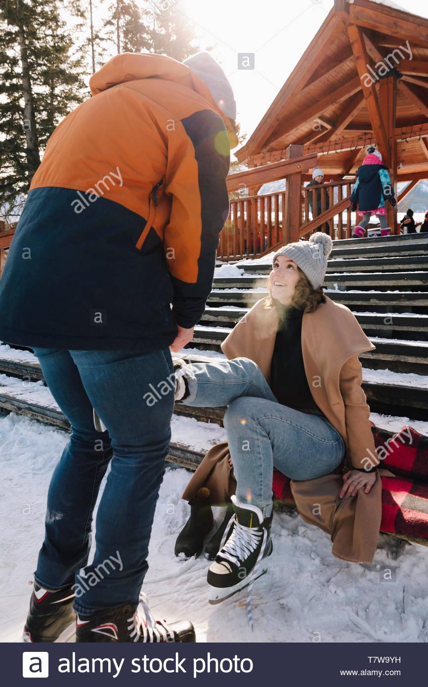 Boyfriend tying girlfriend's ice skate on snowy steps - Stock Image
