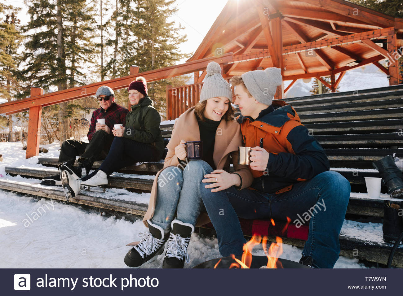 Affectionate teenage couple drinking hot cocoa, taking a break from ice skating Stock Photo