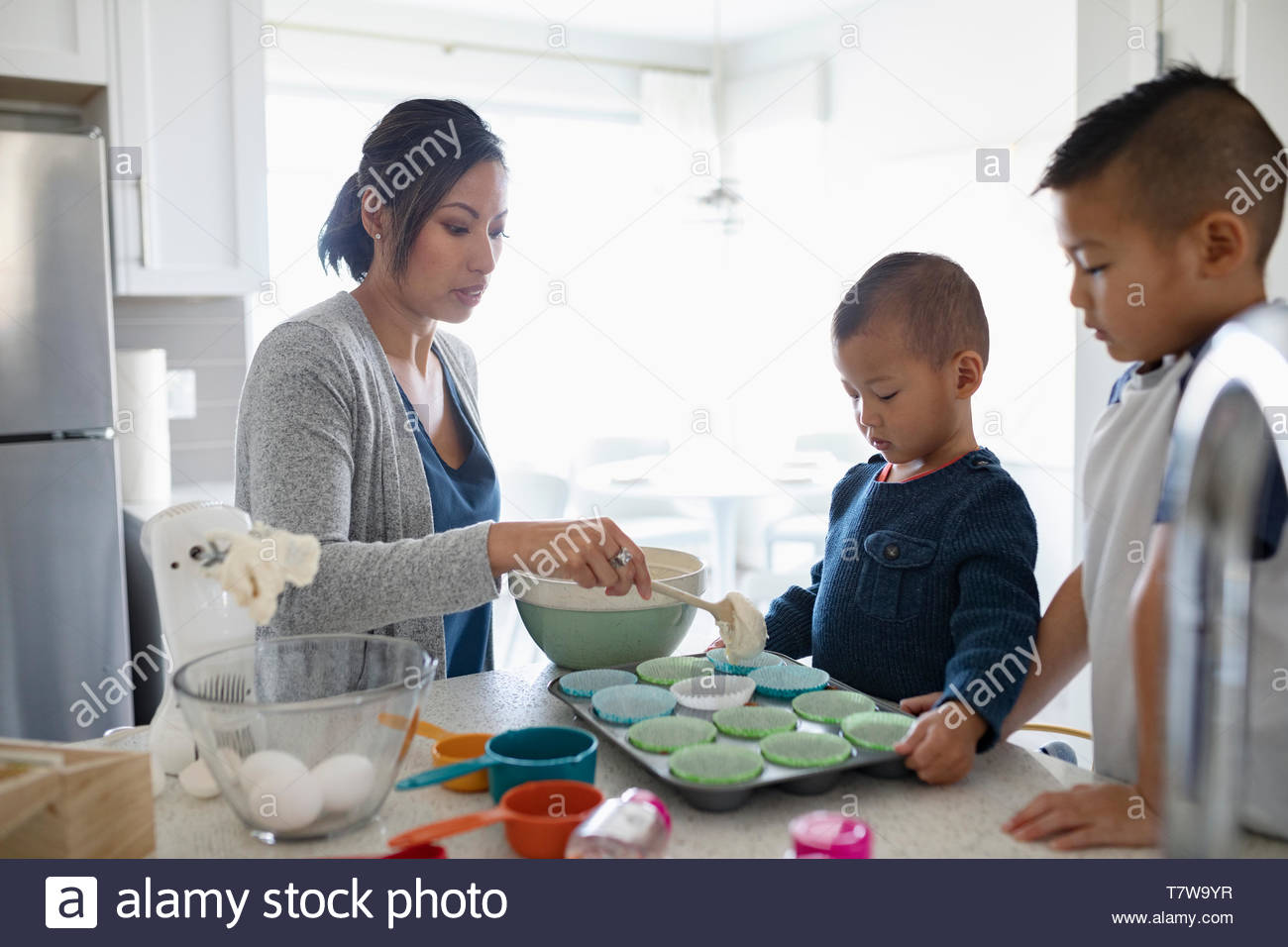 Mother and sons baking cupcakes in kitchen - Stock Image