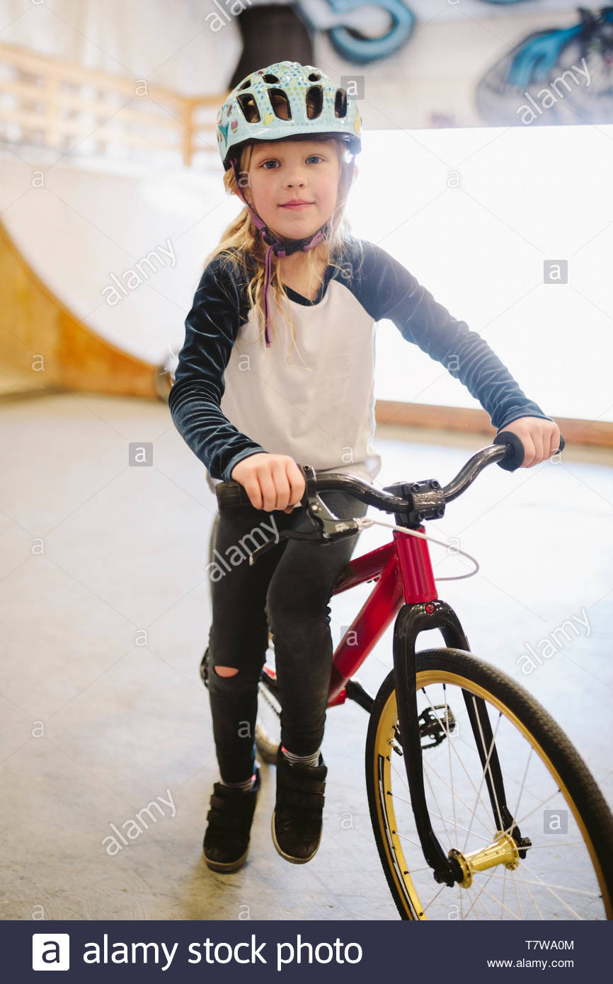 Portrait confident girl with bmx bike at indoor skate park Stock Photo