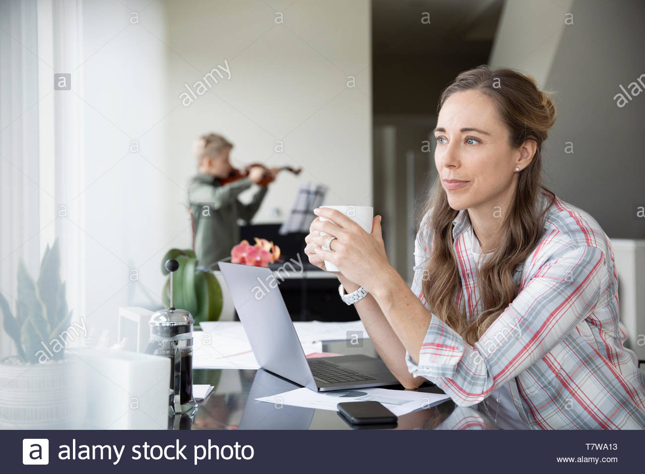Thoughtful woman drinking coffee, working from home while son practices violin in background - Stock Image