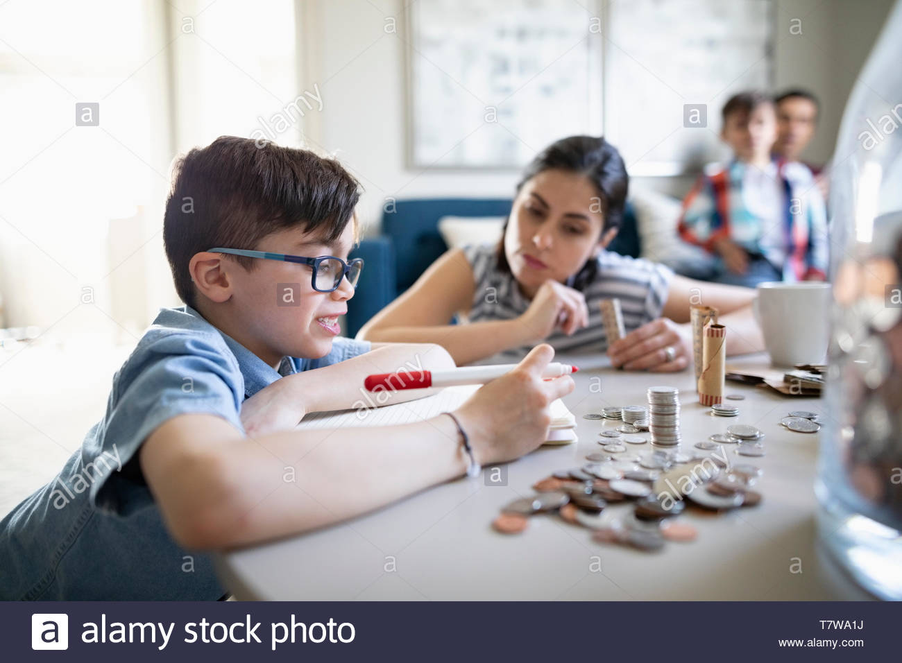 Mother watching son counting allowance money - Stock Image