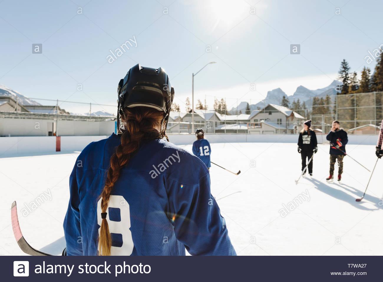 Girl playing outdoor ice hockey Stock Photo