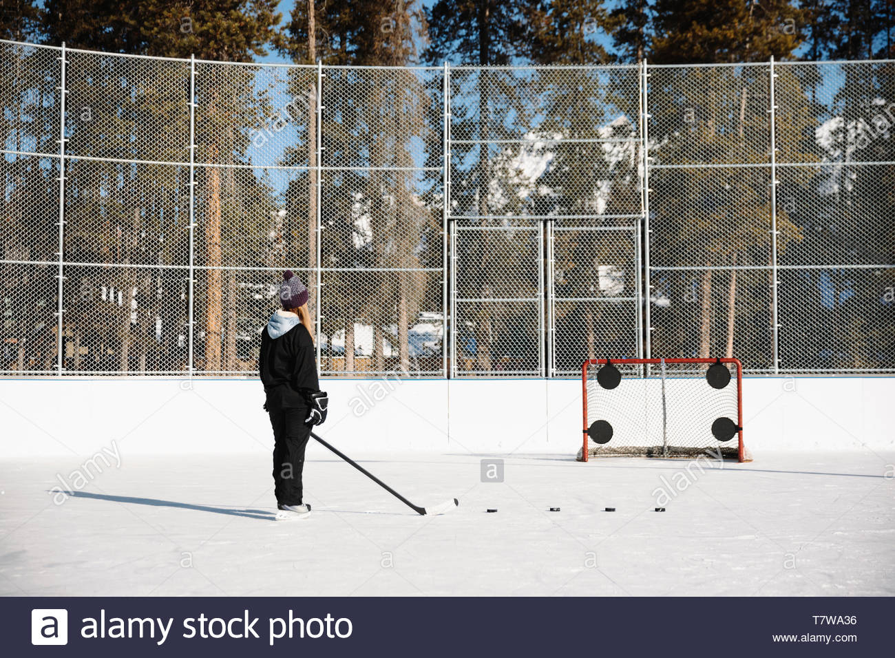 Woman playing outdoor ice hockey, practicing penalty shots - Stock Image