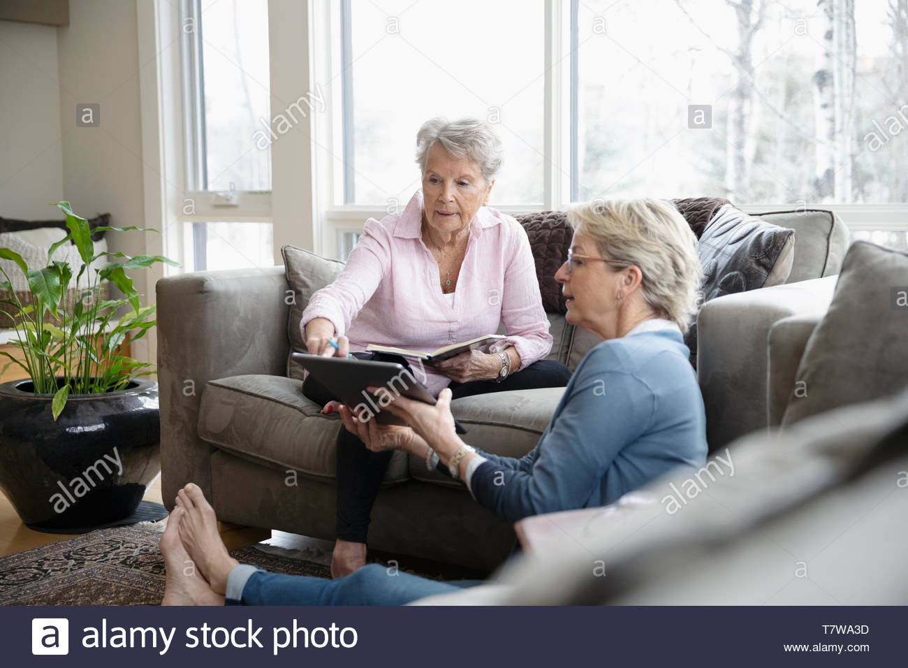 Daughter with digital tablet talking to senior mother in living room - Stock Image