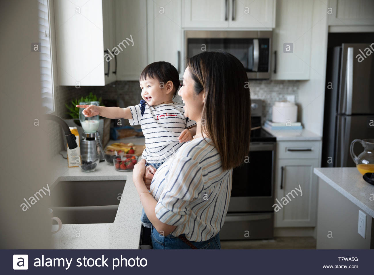 Mother and cute toddler daughter in kitchen - Stock Image
