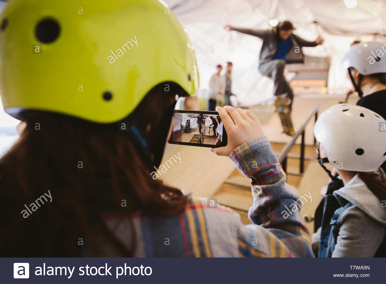 Boy with camera phone filming man skateboarding at indoor skate park - Stock Image