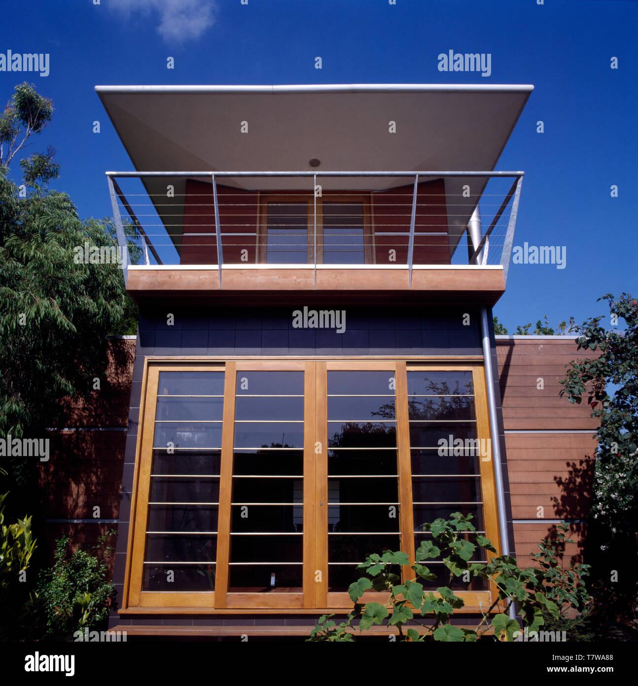 Exterior Of A Modern Architectural House With A Balcony Below An Extended Roof And Above Glass Wood Doors Stock Photo Alamy