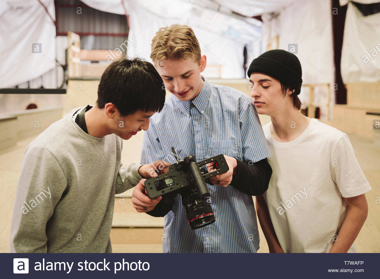 Teenage boys with video camera at indoor skate park - Stock Image