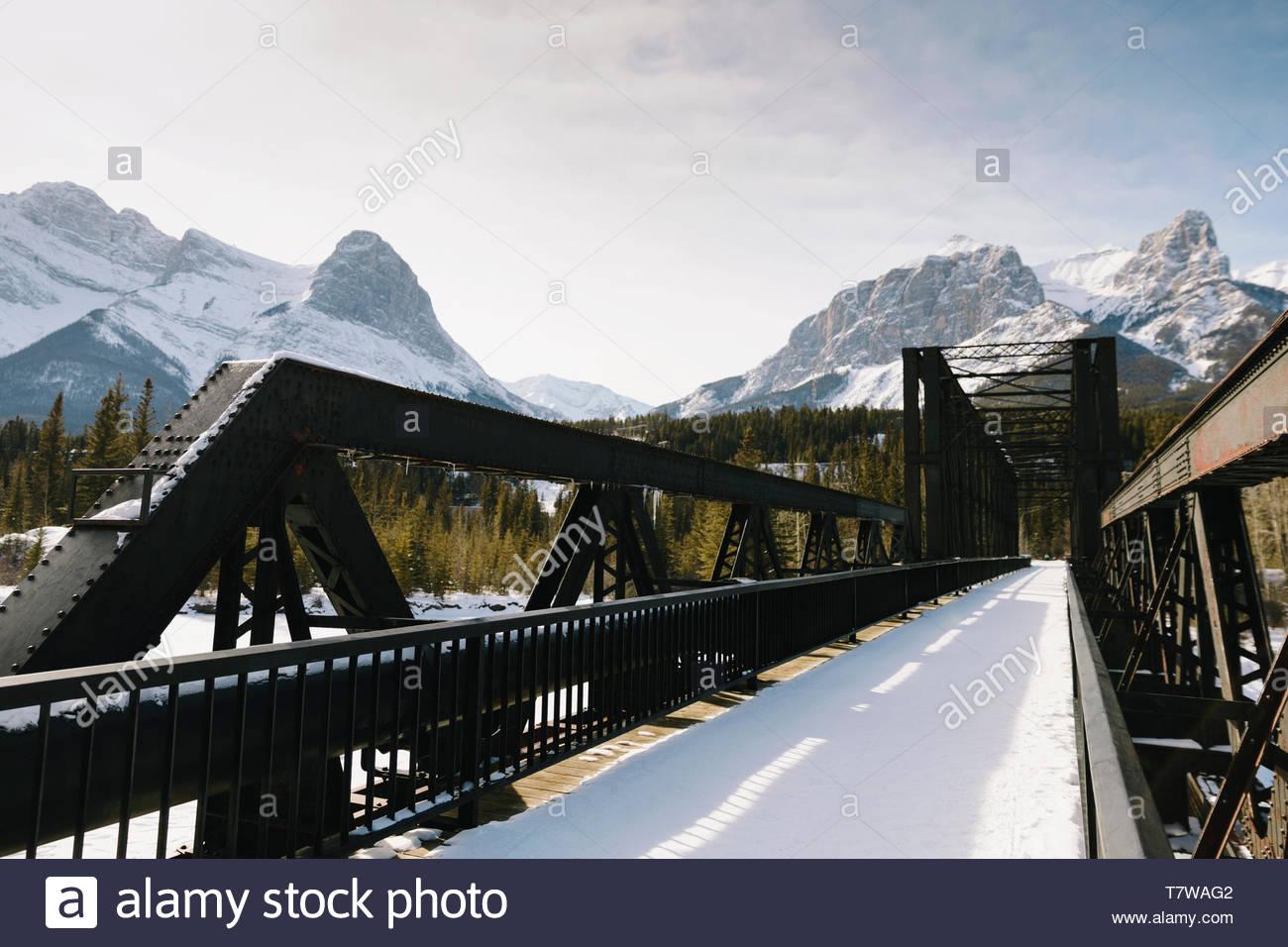 Snow covered bridge below mountains - Stock Image
