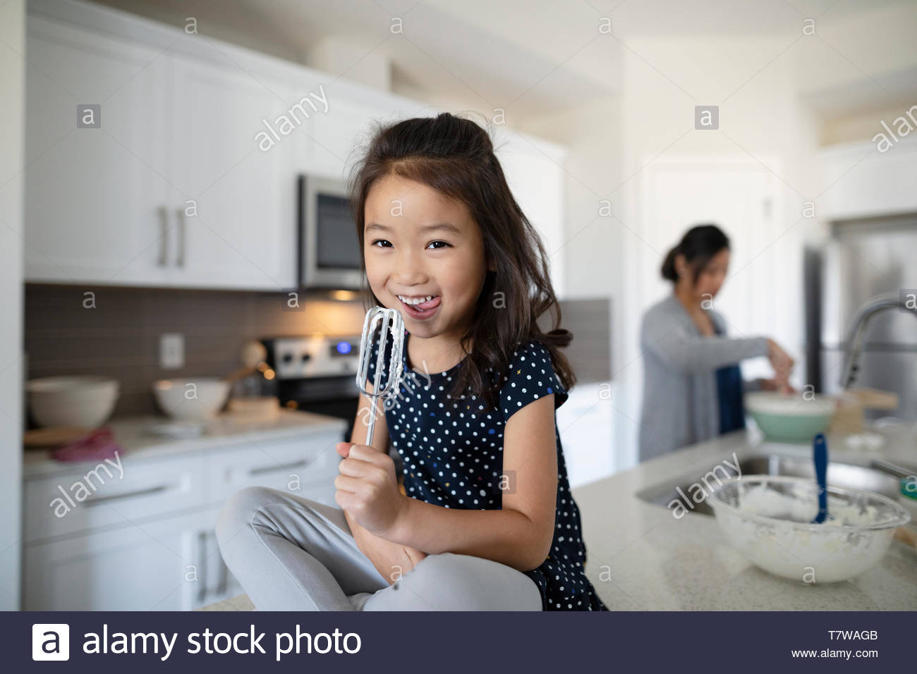 Portrait cute girl licking frosting from beater in kitchen - Stock Image