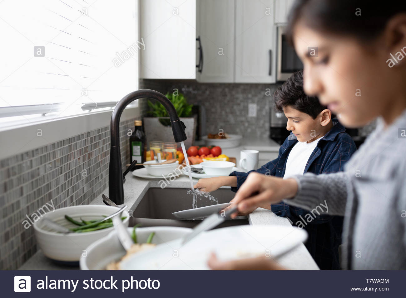 Brother and sister doing dishes at kitchen sink - Stock Image