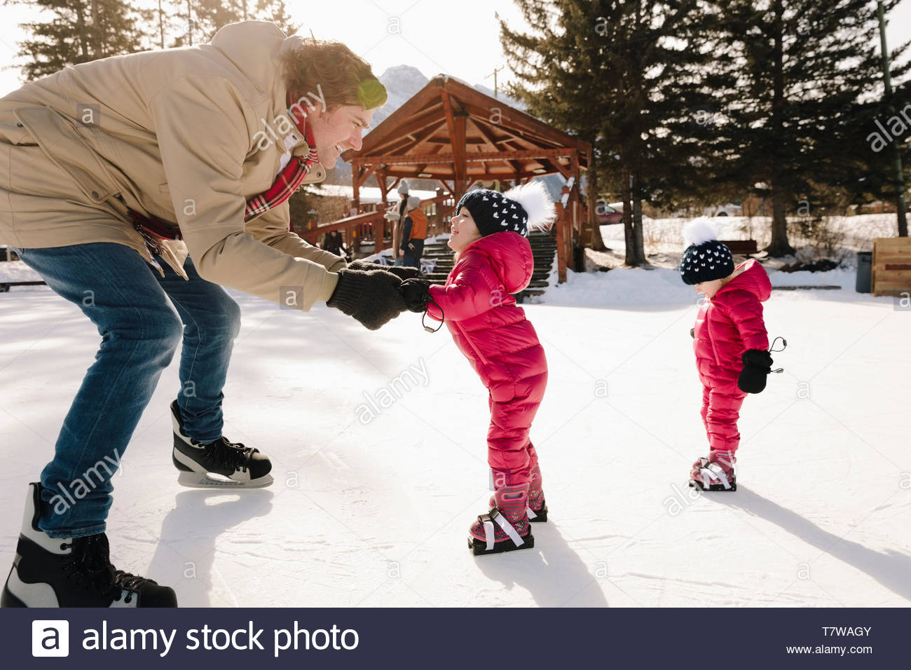 Father and toddler daughter ice skating on frozen pond - Stock Image