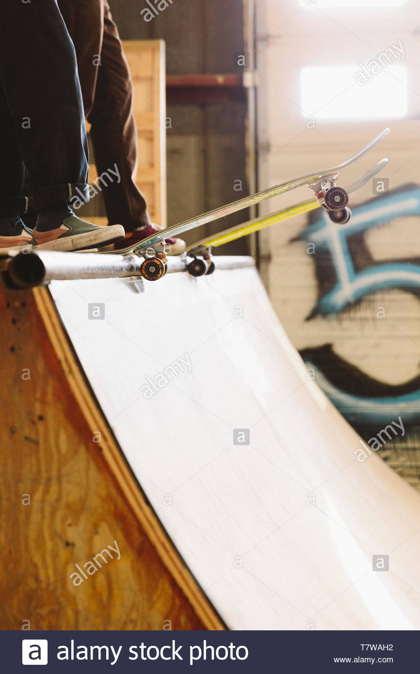 Friends with skateboards at top of ramp at indoor skate park - Stock Image