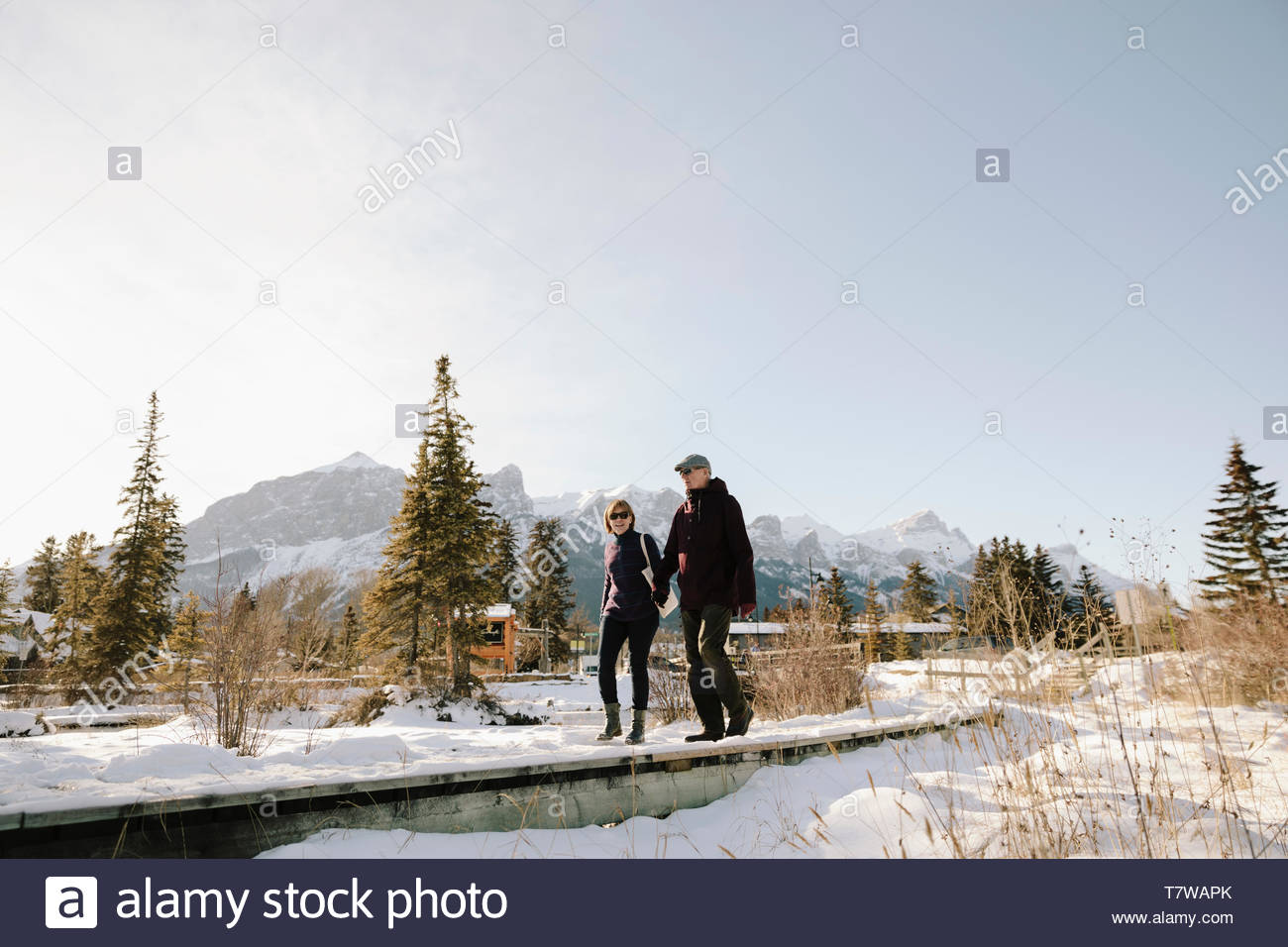 Senior couple walking along sunny, snowy path with mountains in background - Stock Image