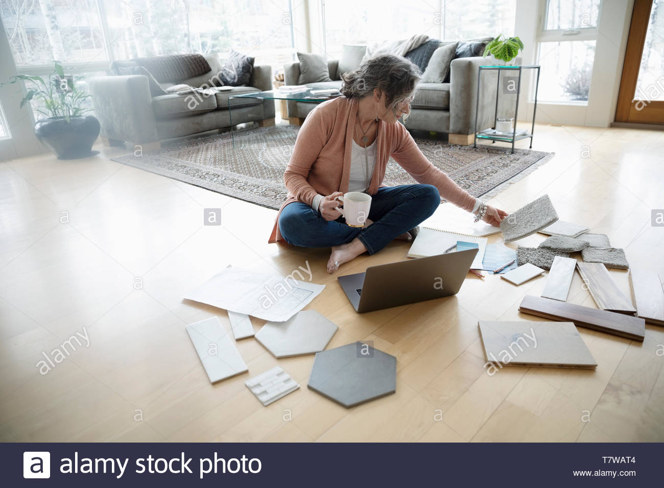 Senior woman redecorating, looking at swatches on floor - Stock Image