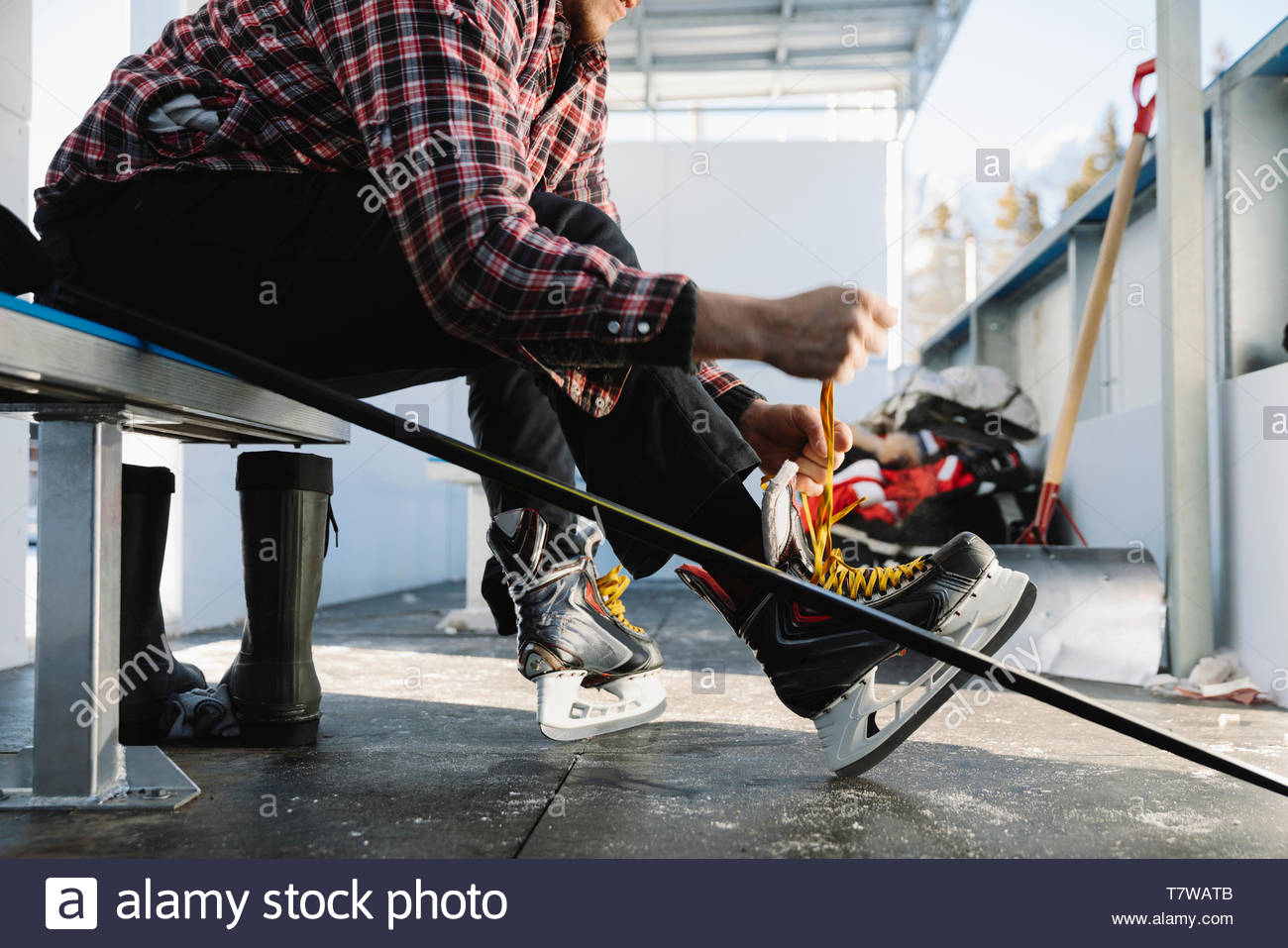 Man tying ice skate, preparing for outdoor ice hockey - Stock Image