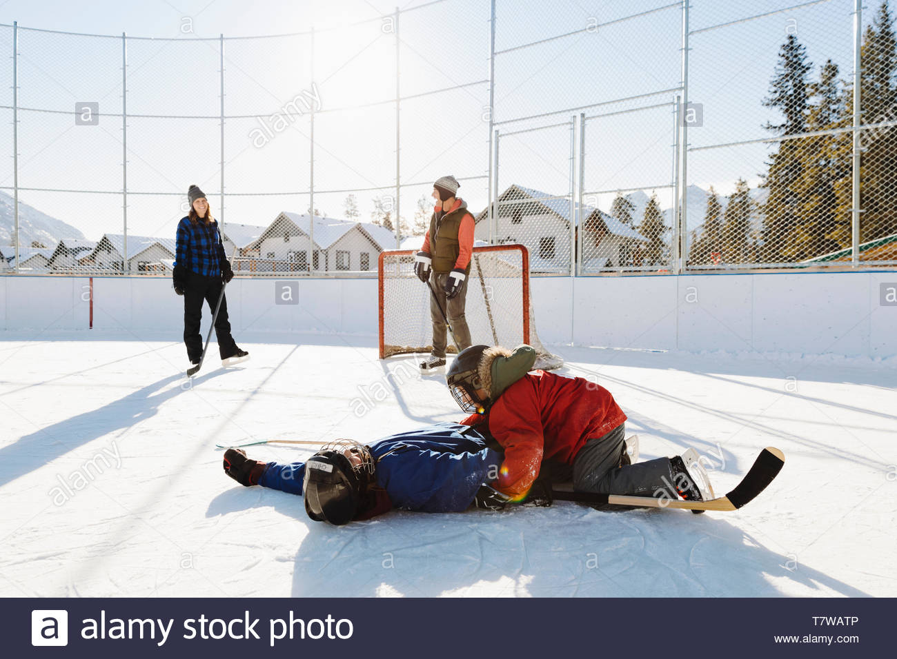 Family playing outdoor ice hockey - Stock Image