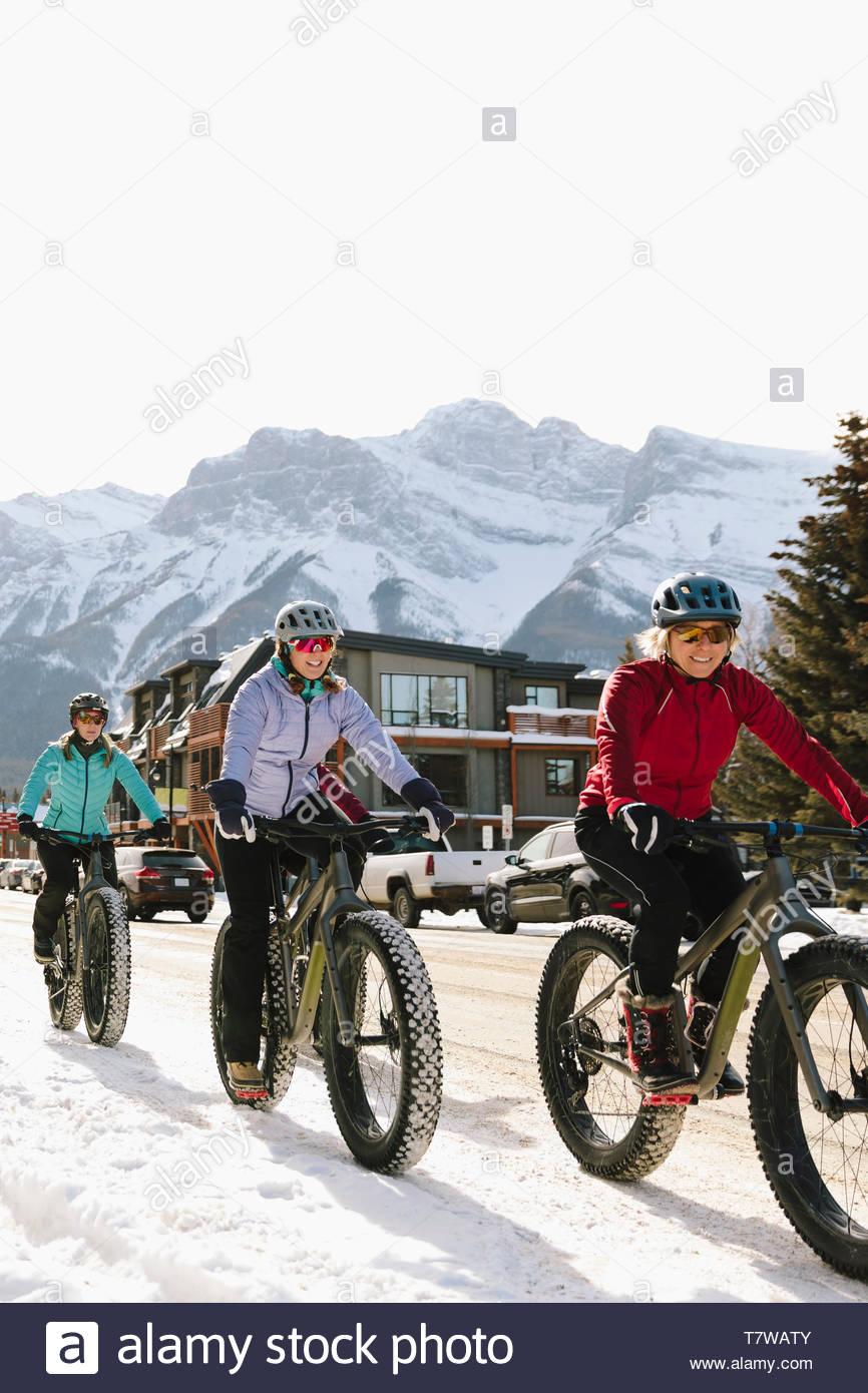 Friends fat biking on snowy road in mountain town - Stock Image