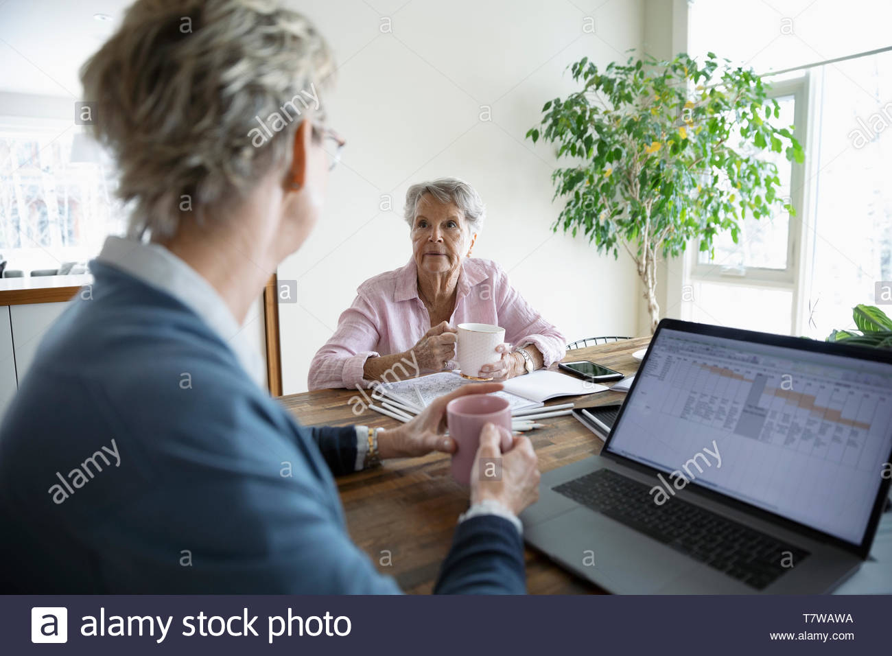 Daughter and senior mother talking, drinking coffee and paying bills online - Stock Image
