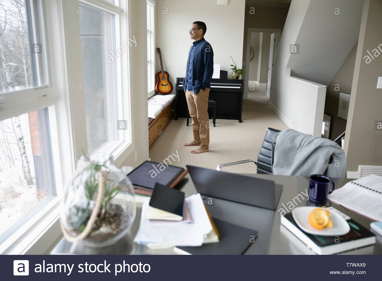 Thoughtful man taking a break from working at home, looking out window - Stock Image