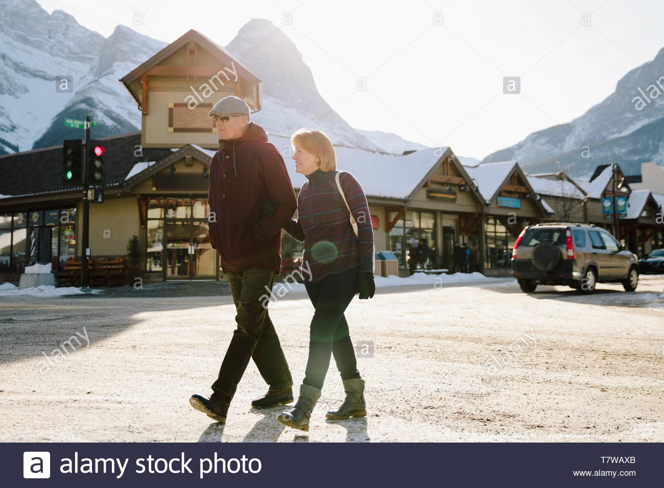 Senior couple walking on sunny, snowy street in mountain town - Stock Image