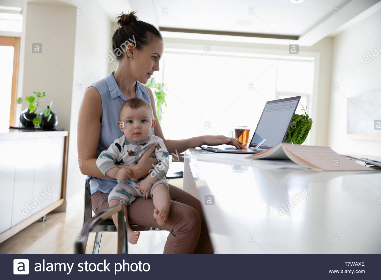 Mother with baby working at home - Stock Image
