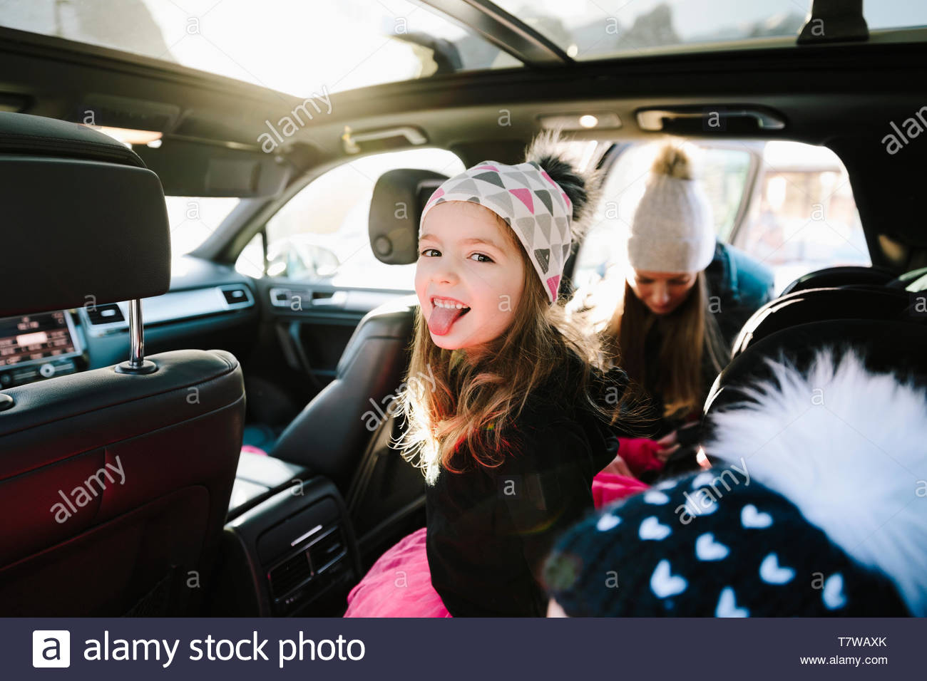 Portrait playful girl in car sticking out tongue - Stock Image