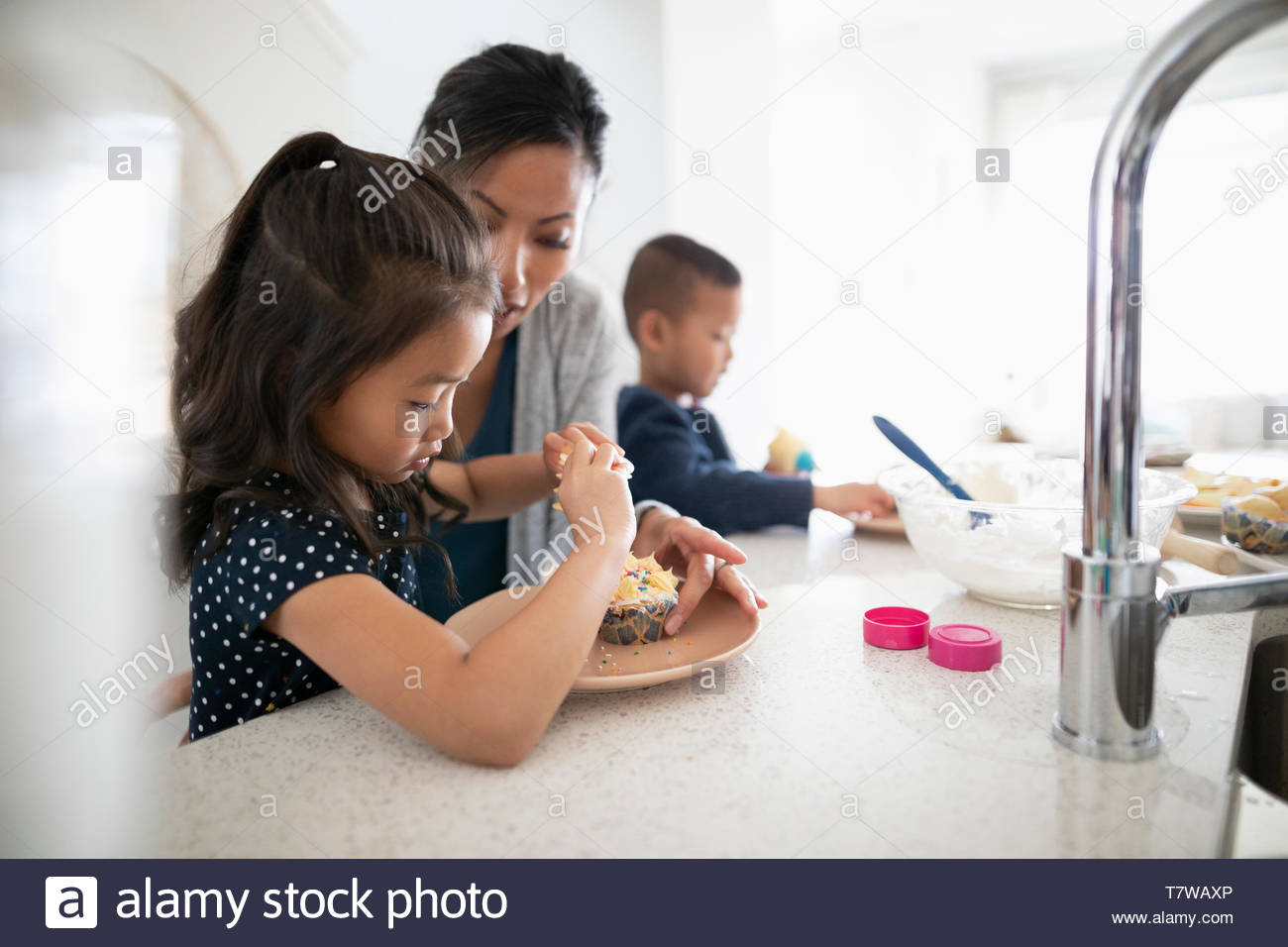 Mother and children decorating cupcakes in kitchen - Stock Image