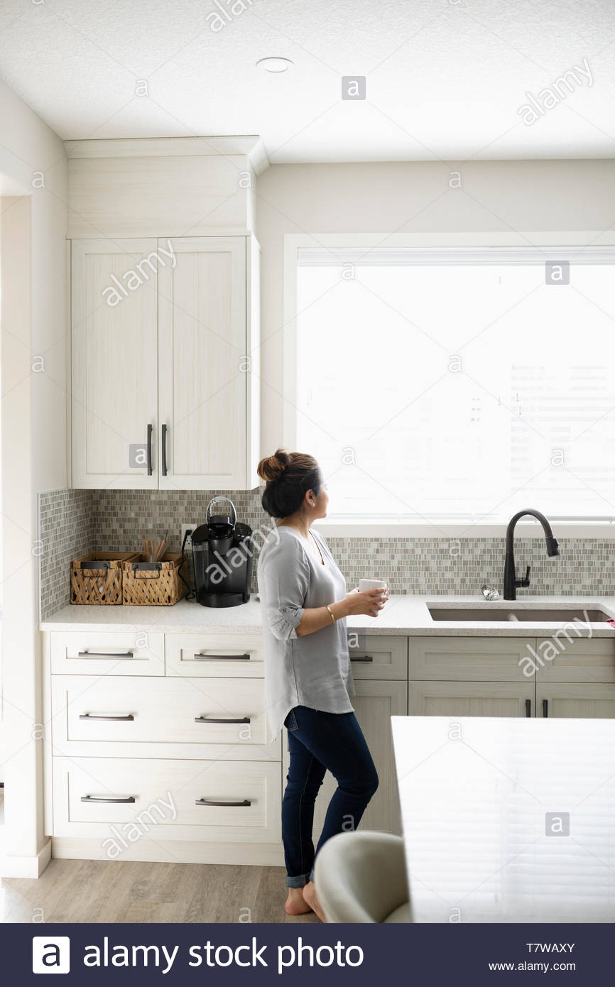 Thoughtful woman drinking coffee and looking out kitchen window - Stock Image