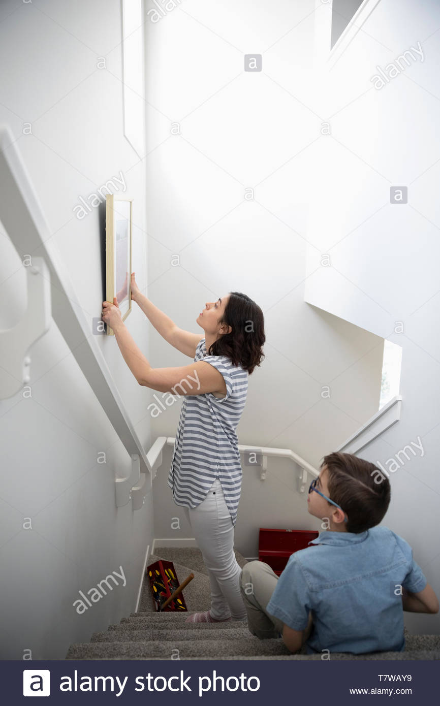 Son watching mother hang picture on wall above stairs - Stock Image