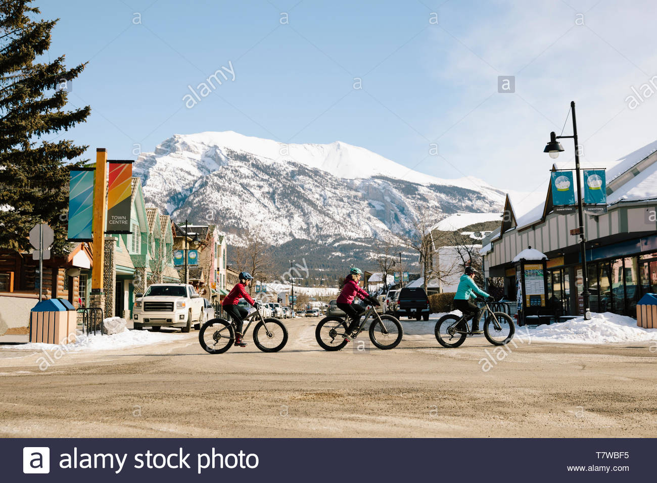Friends fat biking in town below mountain - Stock Image