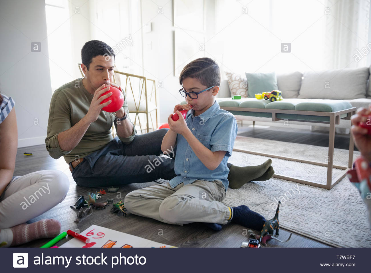 Father and son blowing up birthday balloons in living room - Stock Image