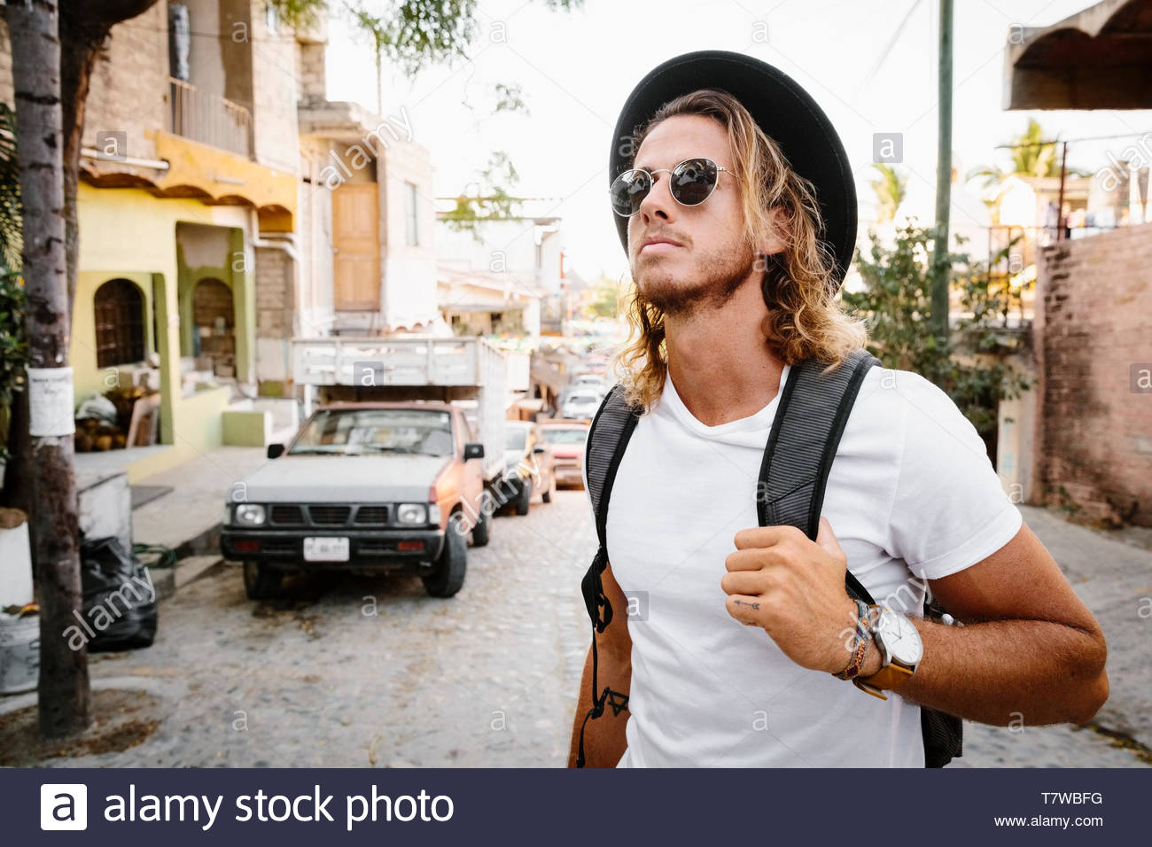Young male tourist walking on street, Mexico - Stock Image