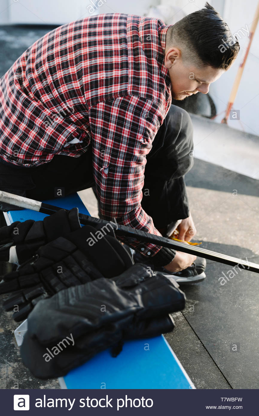 Man tying ice skate, preparing to play outdoor ice hockey - Stock Image