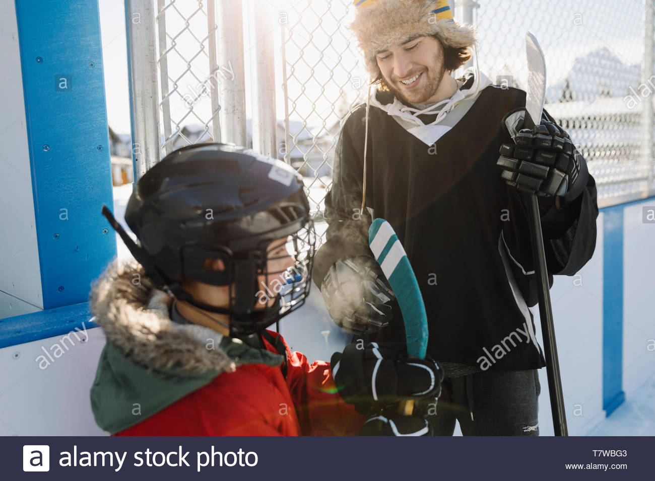Brother and sister playing outdoor ice hockey - Stock Image