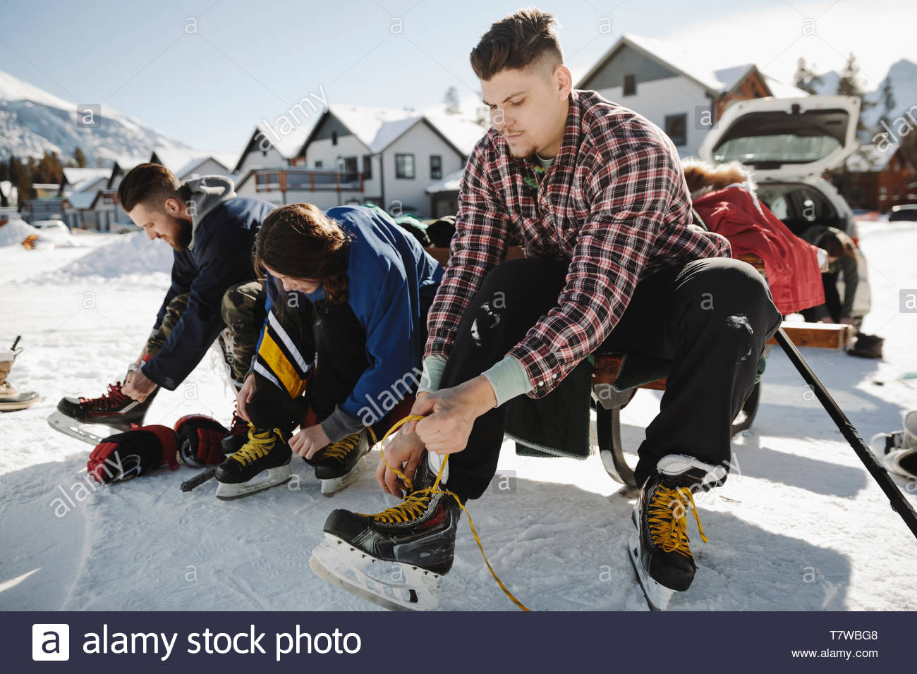 Friends tying ice skates, preparing to play outdoor ice hockey - Stock Image
