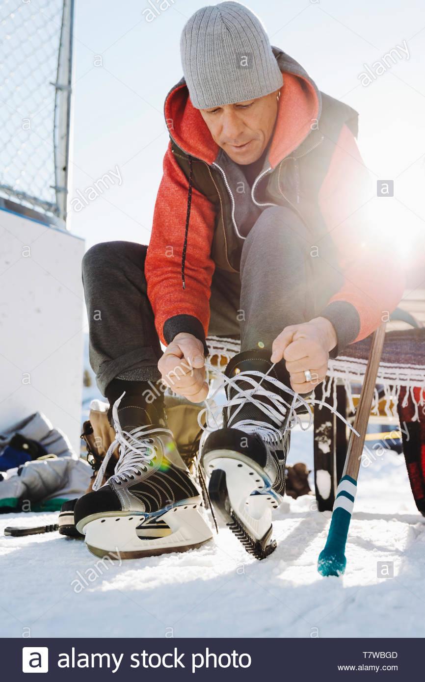 Man tying ice skates in snow - Stock Image