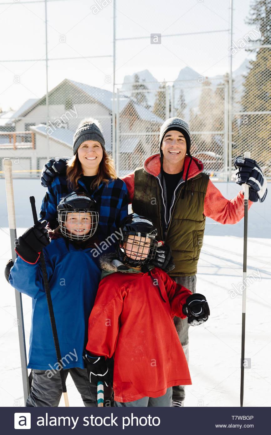 Portrait happy family playing outdoor ice hockey Stock Photo